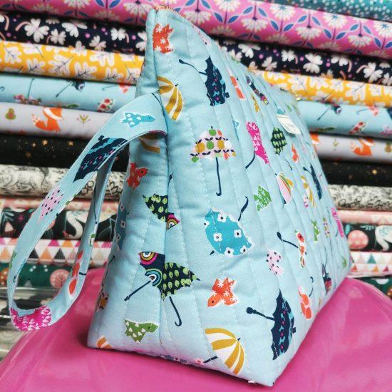 Trousse de toilette pour maman pour bébé en tissu matelassé, imprimé parapluies de chez Dashwood studio